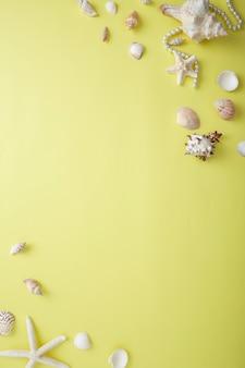 Vista de alto ângulo de conchas por binóculos e jóias sobre amarelo