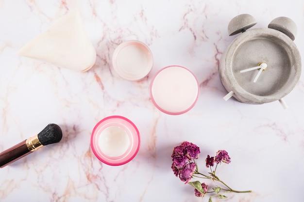 Vista de alto ângulo de creme hidratante; escova; flor e alarme em mármore