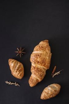Vista de alto ângulo de croissants; especiarias e grãos em fundo preto