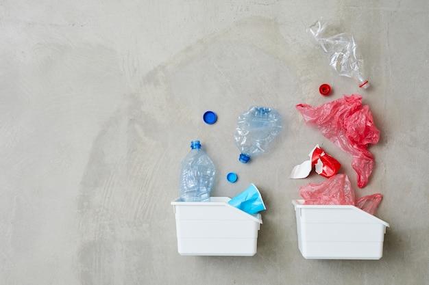 Vista de alto ângulo de dois recipientes de plástico com garrafas de plástico e embalagens isoladas em fundo cinza