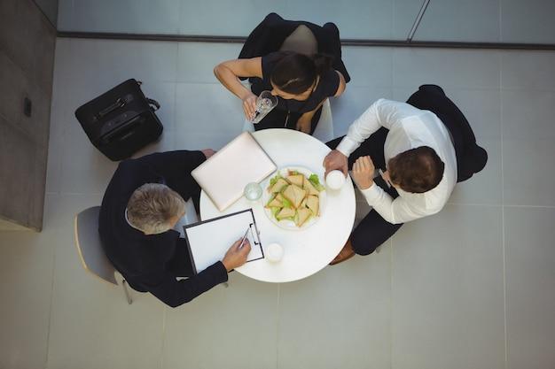 Vista de alto ângulo de empresários tomando café da manhã juntos