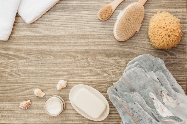 Vista de alto ângulo de esponja; concha do mar; sabonete; escova; toalha e creme hidratante no pano de fundo de madeira