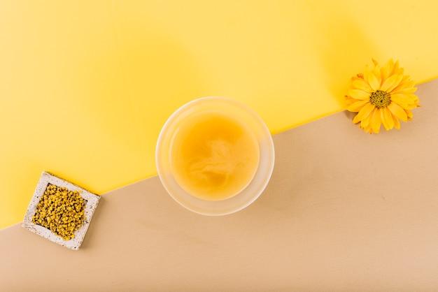 Vista de alto ângulo de flores; coalhada de limão e pólen de abelha em fundo colorido duplo