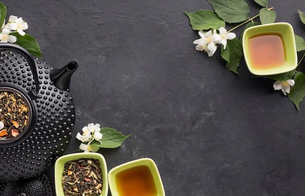 Vista de alto ângulo de folhas secas e chá de ervas no pano de fundo texturizado