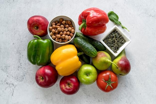 Vista de alto ângulo de frutas coloridas; legumes; sementes de abóbora e avelãs no fundo