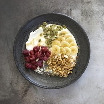 Vista de alto ângulo de iogurte com nozes, framboesas e banana em uma tigela sobre a mesa