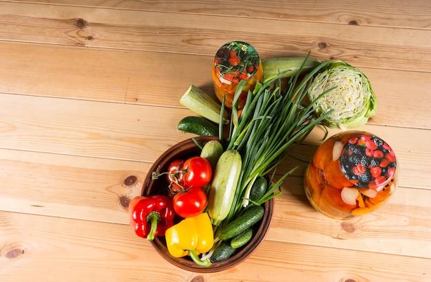 Vista de alto ângulo de legumes frescos e potes de conservas em conserva na superfície da mesa de madeira com espaço para cópia