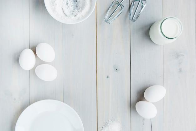 Vista de alto ângulo de leite; farinha; bata e ovos na prancha de madeira