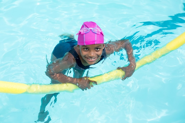 Vista de alto ângulo de menina nadando com macarrão de piscina