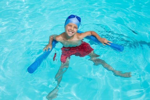 Vista de alto ângulo de menino alegre nadando com macarrão de piscina