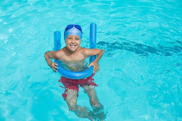 Vista de alto ângulo de menino nadando com macarrão de piscina