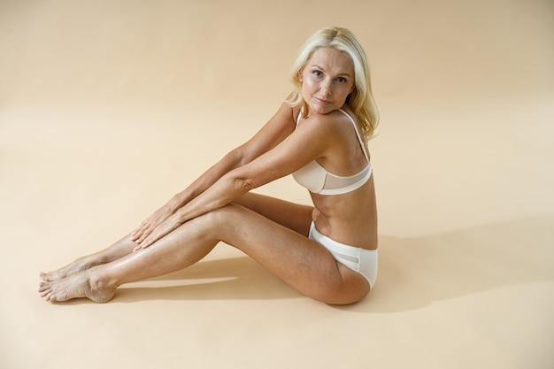 Vista de alto ângulo de mulher loira madura com corpo em forma, posando de cueca, sentada no chão do estúdio
