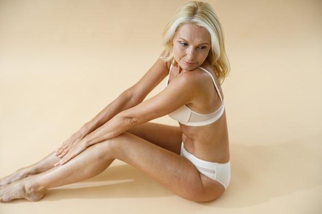 Vista de alto ângulo de mulher loira madura com corpo perfeito, posando de cueca, sentada no estúdio