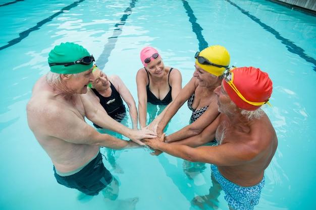 Vista de alto ângulo de nadadores empilhando as mãos na piscina