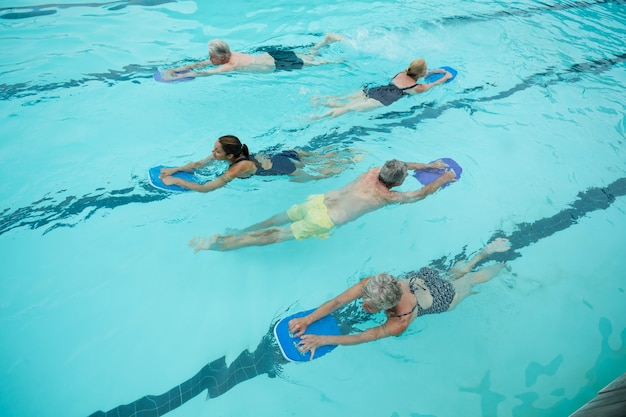 Vista de alto ângulo de nadadores seniores com instrutor de natação na piscina