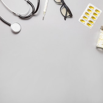 Vista de alto ângulo de óculos; termômetro; estetoscópio e pílulas em fundo cinza