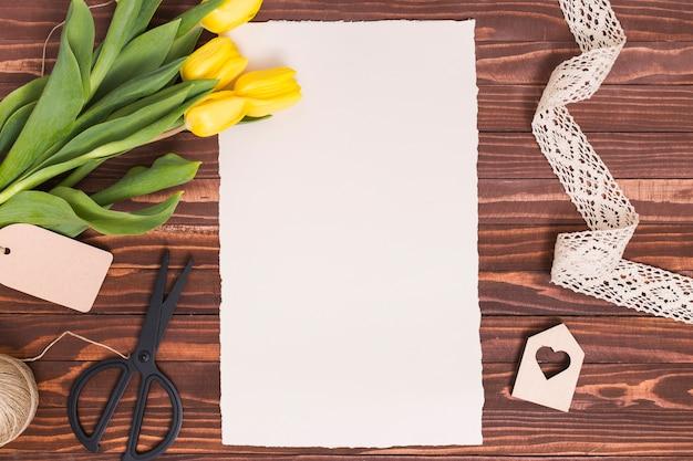 Vista de alto ângulo de papel em branco; flores amarelas; tesoura; corda; forma de coração e laço no pano de fundo de madeira