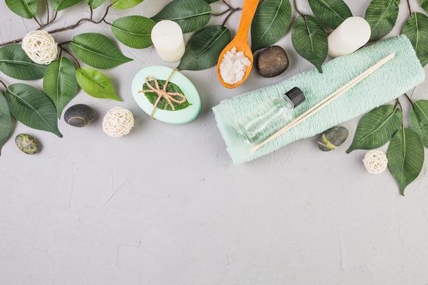 Vista de alto ângulo de pedras spa; toalha; sal; sabonete; folhas e velas no fundo cinza
