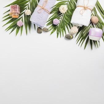 Vista de alto ângulo de pedras spa; toalhas; creme hidratante; esfregue a garrafa e folhas no pano de fundo branco