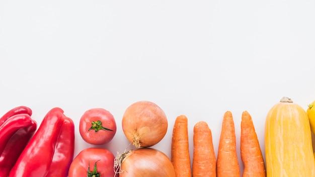 Vista de alto ângulo de pimentão vermelho; tomates; cebolas; cenoura e abóbora na superfície branca