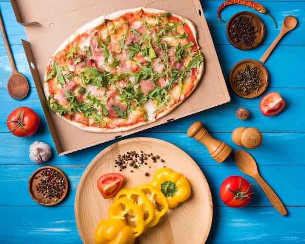 Vista de alto ângulo de pizza; legumes e especiarias contra o pano de fundo de madeira