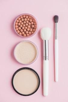 Vista de alto ângulo de pós compactos; pérolas bronzeadoras e pincéis de maquiagem em fundo rosa