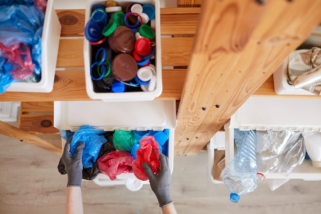 Vista de alto ângulo de prateleiras de madeira com recipientes de plástico para coleta de lixo em casa, armazenamento e conceito de reciclagem