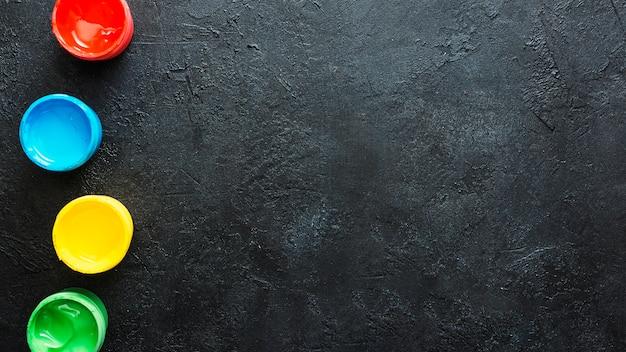 Vista de alto ângulo de recipiente de tinta de cor de água no fundo preto