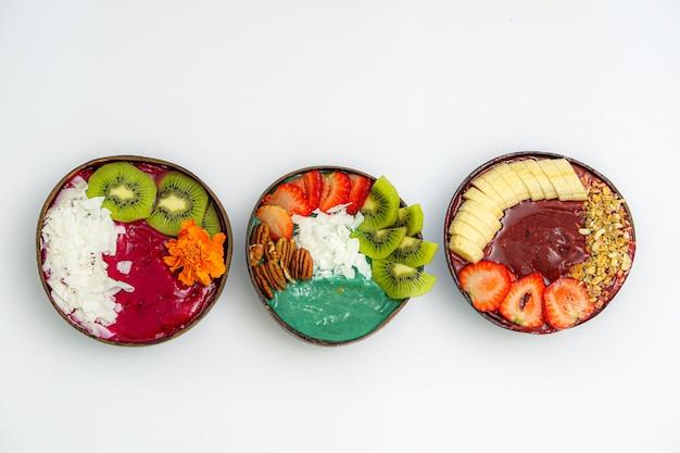 Vista de alto ângulo de tigelas com frutas fatiadas e molhos na mesa branca