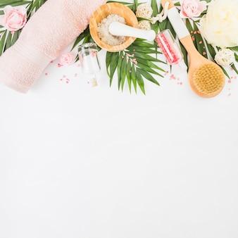 Vista de alto ângulo de toalha; sal; bucha; sai; garrafa; escova e flores falsificadas na superfície branca