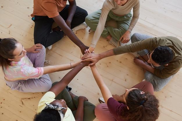 Vista de alto ângulo de um grupo de pessoas sentadas no chão e de mãos dadas, apoiadas umas nas outras