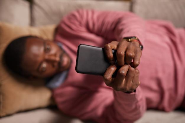 Vista de alto ângulo de um homem africano digitando no celular, trabalhando online enquanto estava deitado no sofá