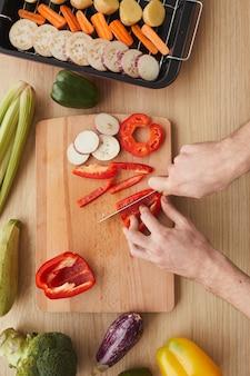 Vista de alto ângulo de um homem cortando vegetais com uma faca na tábua