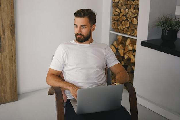 Vista de alto ângulo de um jovem blogueiro moderno com a barba por fazer e um olhar pensativo e pensativo enquanto trabalha em um novo artigo ou postagem para seu blog online, sentado na poltrona com o laptop aberto