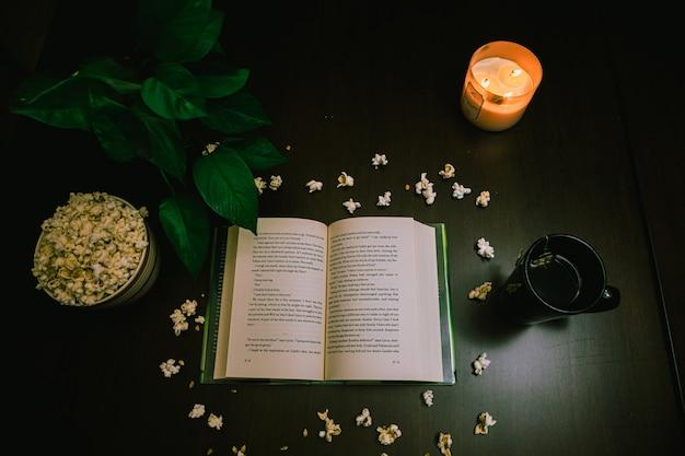 Vista de alto ângulo de um livro aberto e pipoca na mesa com uma vela acesa e uma xícara de chá