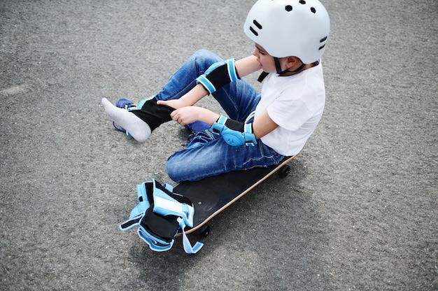 Vista de alto ângulo de um menino esportivo com capacete de segurança sentado no skate no asfalto do parquinho e colocando joelheiras de proteção