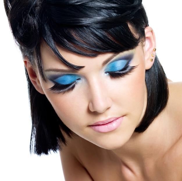 Vista de alto ângulo de um rosto de uma bela jovem com maquiagem azul. isolado no branco