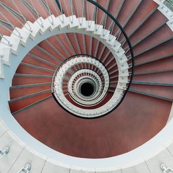 Vista de alto ângulo de uma escada em espiral moderna sob as luzes