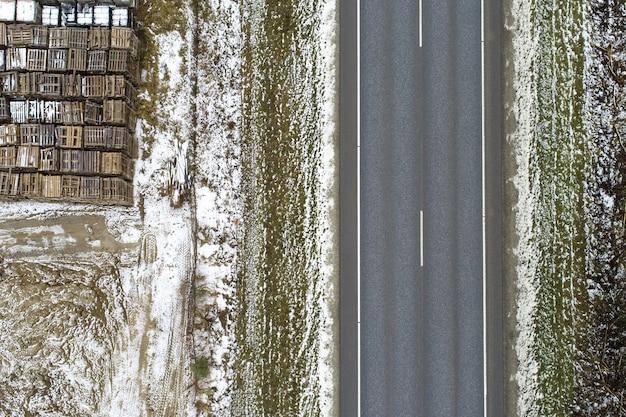 Vista de alto ângulo de uma estrada cercada por um prado coberto de neve com objetos metálicos
