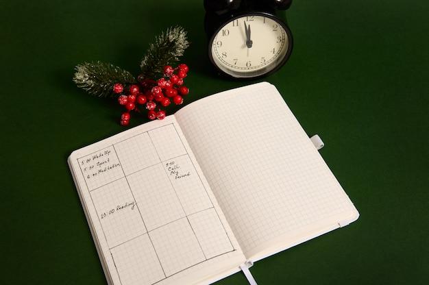 Vista de alto ângulo de uma página aberta do bloco de notas com planos para o dia, despertador e ramo nevado da planta de natal de azevinho isolada em fundo verde