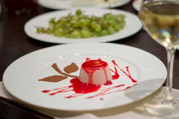 Vista de alto ângulo de uma porção individual de uma deliciosa sobremesa de musse coberta com uma calda de fruta vermelha rica em uma mesa de restaurante com uma taça de vinho branco