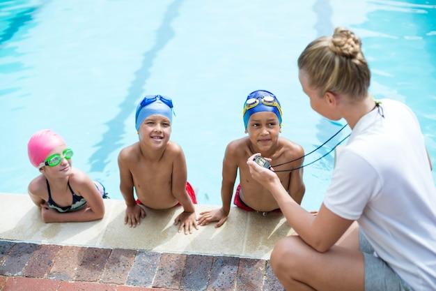Vista de alto ângulo de uma treinadora de natação ensinando alunos ao lado da piscina