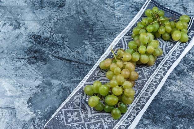 Vista de alto ângulo de uvas frescas no fundo do grunge e toalha de cozinha