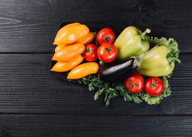 Vista de alto ângulo de vegetais crus saudáveis na superfície de madeira preta