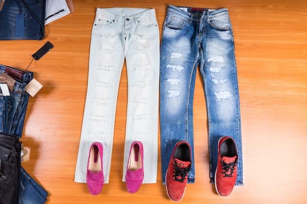 Vista de alto ângulo dele e dela jeans afligidos e rasgados esticados na superfície de madeira com sapatos coordenados - elegantes mocassins rosa e tênis vermelhos