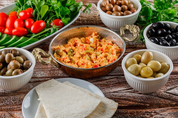Vista de alto ângulo deliciosa refeição em panela com salada, picles em tigelas na superfície de madeira