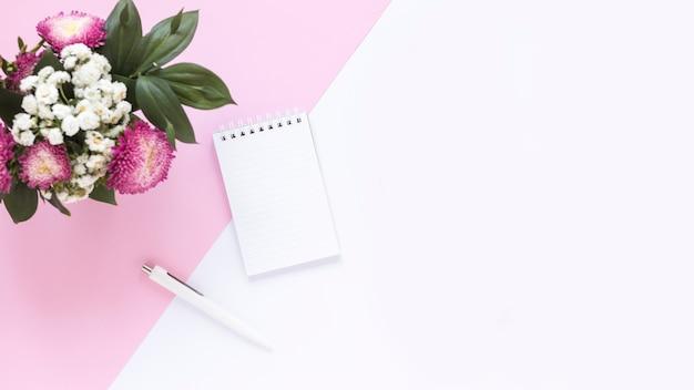 Vista de alto ângulo do bloco de notas em espiral; caneta e ramo de flores em fundo duplo