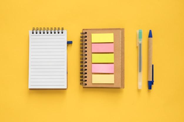 Vista de alto ângulo do bloco de notas em espiral; notas adesivas e caneta em fundo amarelo