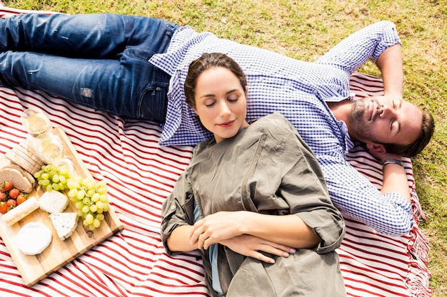 Vista de alto ângulo do casal dormindo na manta de piquenique