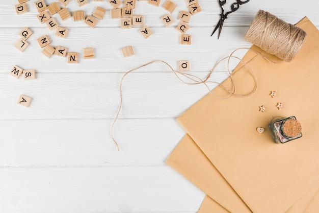Vista de alto ângulo do cubo de texto de madeira; tesoura carretel de corda com papel marrom na mesa branca
